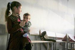 北部ラッカの避難所として使用されている学校で、赤ちゃんを抱く女の子。(2019年10月28日撮影)