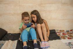 携帯電話でゲームを楽しむセルビアの姉弟。(2019年10月撮影)