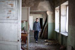 砲撃によって破壊された学校の廊下を歩く14歳のオレクシーさん。(2019年5月撮影)