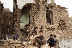 空爆によって破壊された家の前に座るイエメンの子どもたち。(2019年7月撮影)