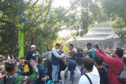 インドネシアの「先生の日」に、ユニセフ水と衛生専門官から月経衛生管理のストーリー教材を手渡されるタンゲラン県知事