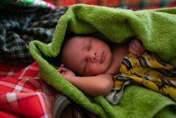 清潔であたたかいタオルにくるまれる、生まれたばかりのウガンダの赤ちゃん。(2019年4月撮影)