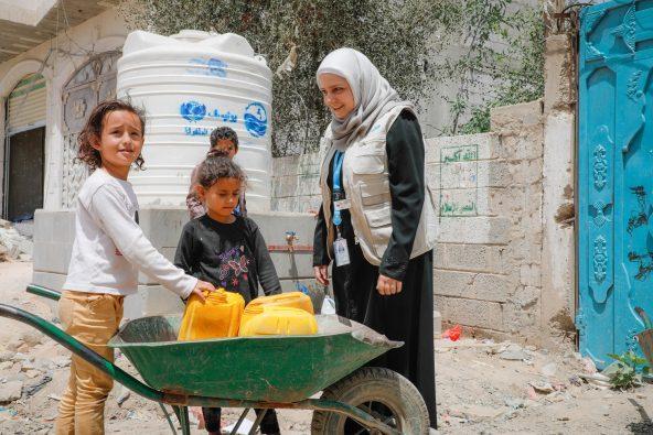 水を汲むために給水車を待つ子どもたちとメイソンさん。