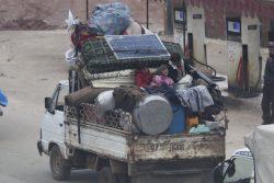 激化する紛争から逃れ、トラックの荷台に乗りイドリブ南部からサルマダに避難する家族。(2020年1月28日撮影)