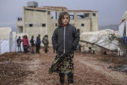 シリア北西部トルコ国境近くの村に設置された非公式居住区で、テントの外に立つ女の子。(2019年12月30日撮影)