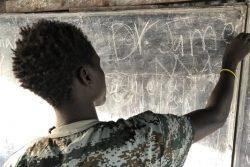 「子どもにやさしい空間」の黒板の前に立ち、「平和」の文字を指さす元子ども兵士のジェームスさん(仮名)。(2020年1月撮影)