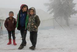 トルコ国境近くの非公式居住区で、厳しい寒さの中テントの外に立つ子どもたち。(2020年2月13日撮影)