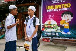 小学校の側にある屋台で購入したファストフードを食べるバンクラデシュの男の子たち。(2019年9月撮影)