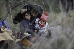 トルコとギリシャの国境近く、エディルネ県パザルクレ(Pazarkule)で、父親に身を寄せる子どもたち。(2020年2月29日撮影)