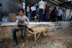 シンジャール村の食品流通センターで、食料の配給を待つ男の子。