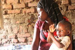 2歳の赤ちゃんを抱くミリアさん。12歳のときに強制結婚させられて妊娠し、学校をやめなければならなかった。(2018年2月撮影,ウガンダ)