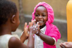 友達と一緒に石けんで手を洗うルワンダの3歳の女の子。(2019年9月撮影)