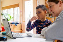 お菓子を食べながら遠隔授業の課題に取り組む8歳のルカくん。ルカくんの通う米国・コネチカット州の小学校は、13日から臨時休校となっている。(2020年3月20日撮影)
