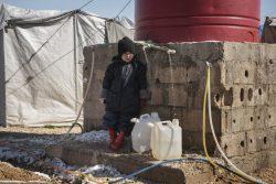 シリア北東部のロジ・キャンプで水を汲む子ども。(2020年2月11日撮影)