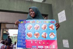 ナイジェリアで行われた新型コロナウイルスの予防イベントに参加し、正しい手洗いの方法を紹介するポスターを持つ9歳のファルディダさん。(2020年3月20日撮影)