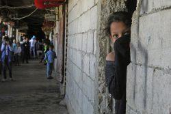 難民シェルターとして使用されている工事中の建物で、口を覆って部屋の外を眺めるシリア難民の女の子。(2020年3月17日撮影)