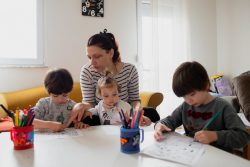 北マケドニアの自宅で1歳のステラちゃんの面倒を見ながら、5歳のマクシムくんとジャンくんの双子の兄弟の勉強を見る母親。(2020年3月25日撮影)