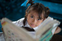 小学校で本を読むカンボジアの女の子。