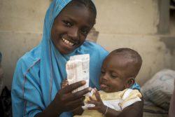 すぐに食べられる栄養治療食(RUTF)を子どもに与える母親。(2020年3月12日撮影)