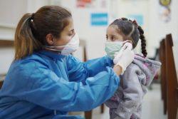 ベイルートのプライマリ・ヘルスケア・センターで、女の子の体温を計る看護師。(2020年4月3日撮影)