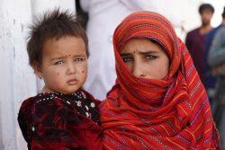 アフガニスタン西部・ヘラートの国内避難民キャンプにある栄養センターの前で、妹を抱く12歳のヤスミンさん。(2019年12月撮影)※本文との直接の関係はありません