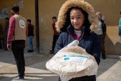 シリア・アレッポ近くのal-Zebdiehで、袋にCOVID-19周知のためのシールが貼ってあるパンを持つ12歳のナジャーフさん。(2020年4月2日撮影)※本文との直接の関係はありません