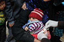 シリア・ラッカにあるMahmoudliキャンプで、上腕計測メジャーを使い栄養不良の検査を受ける赤ちゃん。(2020年3月29日撮影)