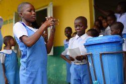 小学校の生徒たちの前で正しい手洗いを実演する子どもたち。 (ナイジェリア、2020年3月18日撮影)