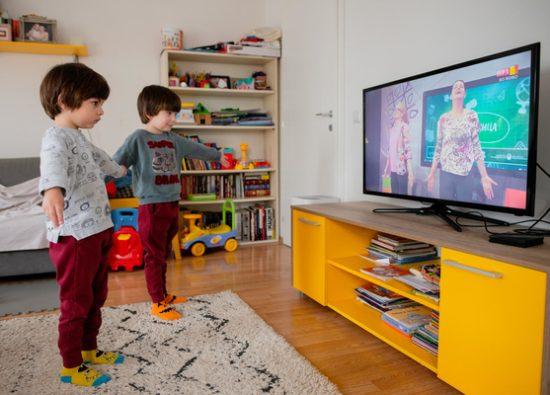 全国放送のテレビ教室プログラムを見ながら、ヨガの練習をする5歳のマクシムくんとジャンくんの双子の兄弟。(北マケドニア、2020年3月25日撮影)