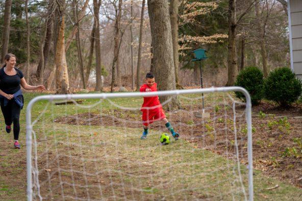 遠隔授業の合間に母親とサッカーを楽しむ8歳のルカくん。(米国、2020年3月17日撮影)