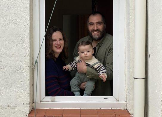 自宅の窓から近所の人による人形劇を鑑賞する生後7カ月のレオンちゃんと両親。(スペイン、2020年3月30日撮影)