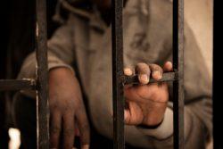 拘留施設の門に手をかけるニジェール移民の14歳の子ども。(リビア、2017年1月撮影)