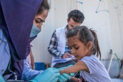 はしかとポリオの予防接種を受けるシリア難民の女の子。サヘラの国境地点から入国する15歳以下のすべての子どもは、ユニセフの支援で予防接種を受けることができる。(イラク、2019年10月撮影)