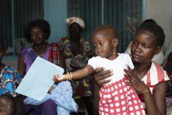 はしかの予防接種を受けるためにやって来たプライマリ・ヘルスケア・センターで、予防接種カードで遊ぶ生後9カ月のクリスティーンちゃん。(南スーダン、2020年3月24日撮影)