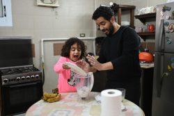 カイロの自宅で待機している間、父親とスムージー作りを楽しむ女の子。(エジプト、2020年3月27日撮影)