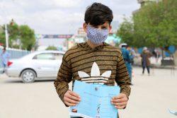 マザーリシャリーフでCOVID-19啓発のためのリーフレットを手にする男の子。(アフガニスタン、2020年4月15日撮影)