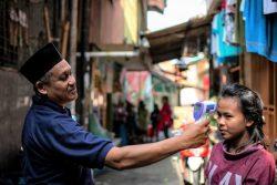 ジャカルタの低所得者層が多く住む地域で、赤外線体温計を使って体温を測ってもらうザハラさん。(インドネシア、2020年4月1日撮影)