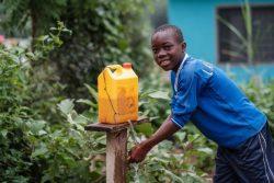 ティッピー・タップと呼ばれる簡易給水器で手を洗うガーナの子ども