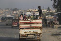 激化する紛争から逃れ、イドリブ南部からアレッポ県北部のアザズ地区にトラックの荷台に乗って避難する家族。(シリア、2020年1月27日撮影)