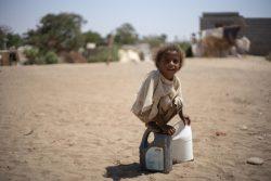 ラヒジュ県の国内避難民キャンプで、給水タンクで汲んだ水が入った容器で遊ぶ女の子。(イエメン、2019年2月撮影)