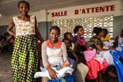 キンシャサ郊外にある診療所で、2人の子どもにはしかの予防接種を受けさせるため、助産師の女性と一緒に待つ母親。(2020年1月27日撮影)
