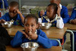 ハウテン州・シャープビルにある小学校で、温かい給食を食べる2年生の生徒たち。(南アフリカ共和国、2019年9月撮影)