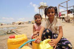 アデンのアル・シャーブ(Al Sha'ab)キャンプで、容器に水を汲む10歳のムナさん。(2020年4月27日撮影)