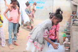 アデンのオマール・ビン・ヤセール(Omar Bin Yasser)キャンプの給水所で、容器に水を汲む子どもたち。(2020年4月27日撮影)