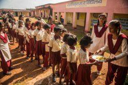 ジャールカンド州・ラーンチーにある政府のモデル校で、列に並んで給食を受け取る子どもたち。(インド、2019年9月撮影)