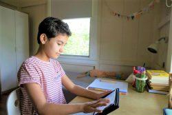 コロン県・ガンボアの自宅で、タブレットを使ってオンライン授業を受ける11歳のミラさん。(パナマ、2020年4月17日撮影)