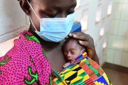 北部コロゴの病院で生後10日の赤ちゃんを抱く女性。母親が三つ子の出産時に亡くなってしまったため、女性と3人の姉妹が赤ちゃんの世話をしている。(コートジボワール、2020年4月28日撮影)
