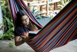 パナマ・ガンボアで勉強の後に自宅の外にあるハンモックの中で読書をする15歳のローラさん。(2020年4月17日撮影)
