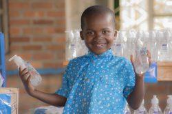 ユニセフから届いたアルコール消毒液のボトルを持つビンセントくん。(ルワンダ、2020年5月4日撮影)