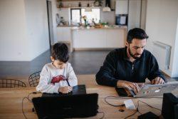 自宅で仕事をする父親の隣で、パソコンを使って遠隔授業を受ける7歳のダニーくん。(アルメニア、2020年4月14日撮影)